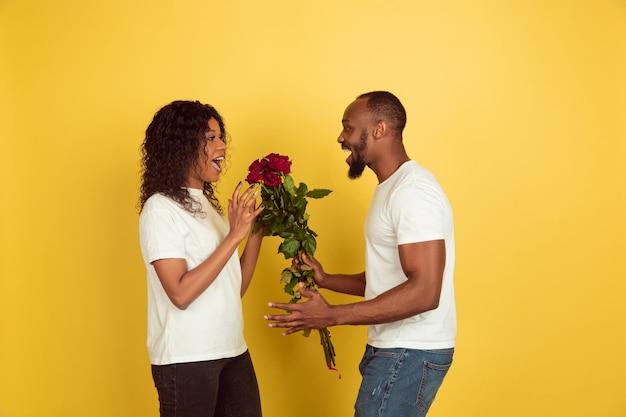 Bloemen voor een glimlach. valentijnsdagviering, gelukkig afrikaans-amerikaans paar dat op gele studioachtergrond wordt geïsoleerd.