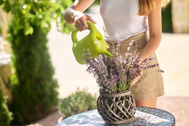 Bloemen water geven. vrouwelijke handen zachtjes zacht drenken delicate bloemen in pot op tuintafel op zonnige dag, zonder gezicht