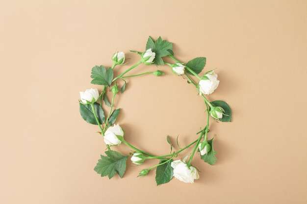 Bloemencirkel op beige lichtbruine achtergrond. rond frame van witte rozen. minimalistische bloemsierkunst compositie