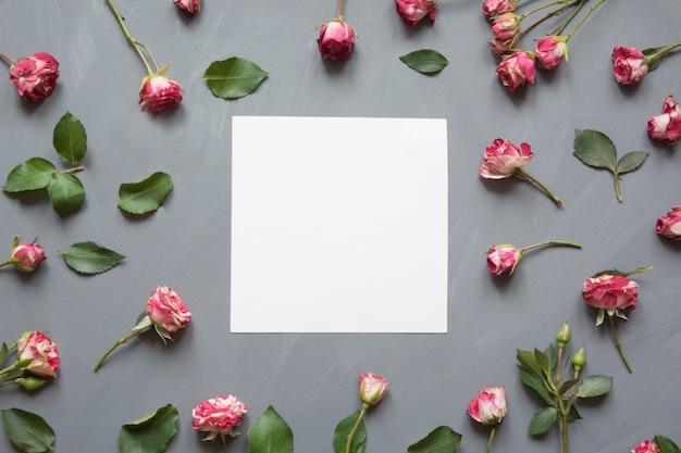 Bloemendiepatroon van roze struikrozen, witte lege, groene bladeren op grijs wordt gemaakt