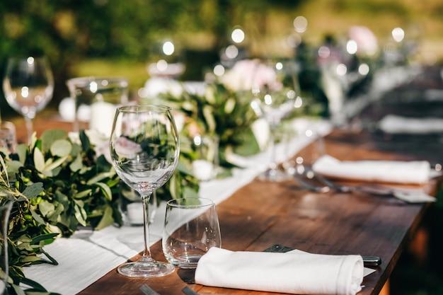 Bloemenguirlande van eucalyptus ligt op de bruiloftstafel