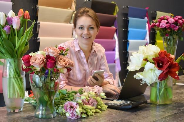 Bloemenhandel. bloemenwinkel. vrouw bloemist een bestelling opnemen. bloemen bezorgen