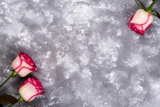 Bloemenkader: boeket van roze witte rozen op steenachtergrond met exemplaarruimte voor tekst.