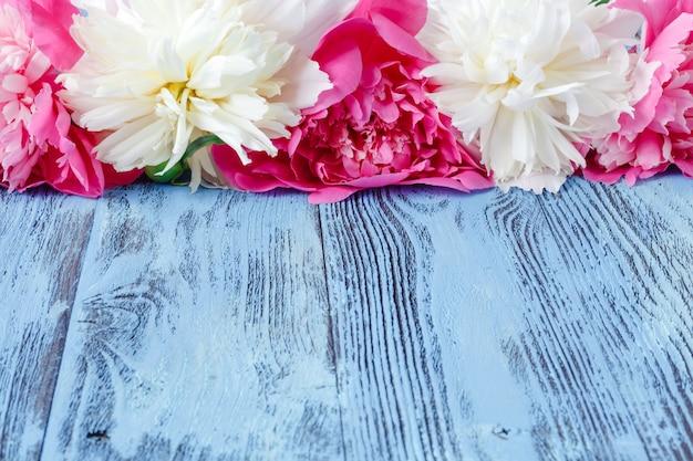 Bloemenkader met roze pioenen op houten