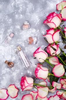 Bloemenkadersamenstelling met rozen en vele verschillende parfumflessen op steenachtergrond.