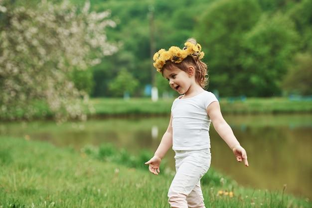 Bloemenkrans is op het hoofd. kind plezier buiten wandelen in het voorjaar
