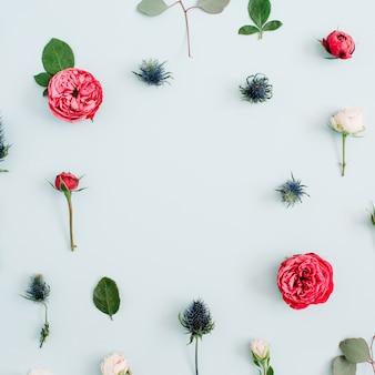 Bloemenlijst gemaakt van beige en rode rozen, eucalyptustakken op licht pastelblauw