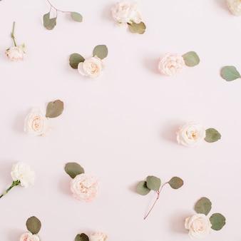 Bloemenlijst gemaakt van beige rozen, eucalyptustakken op bleek pastelroze