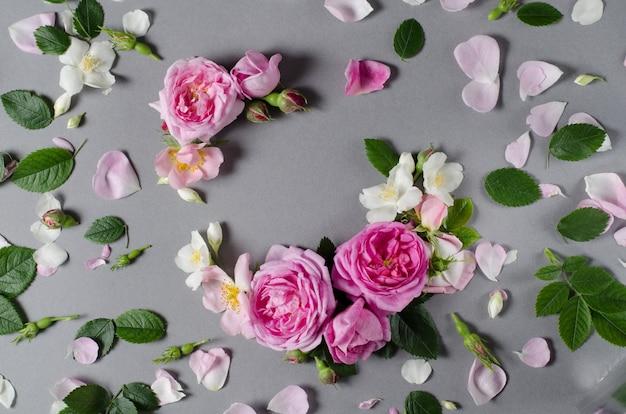 Bloemenlijst. roze bloemen op een grijze achtergrond. plat leggen