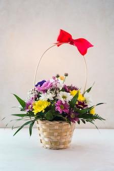 Bloemenmand met rode boog op witte lijst