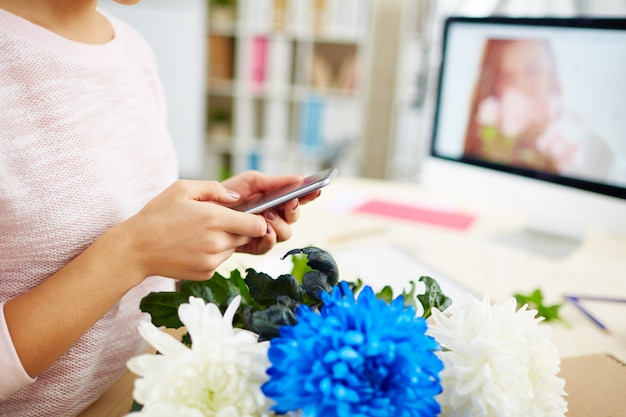 Bloemenontwerper met smartphone