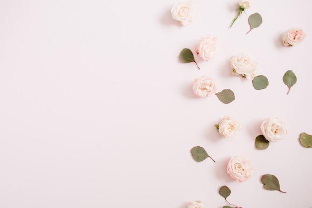 Bloemenpatroon gemaakt van beige rozen, eucalyptustakken op bleek pastelroze