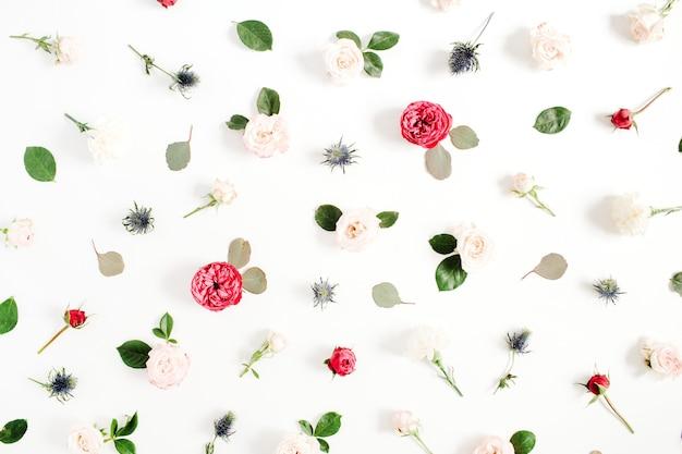 Bloemenpatroon gemaakt van rode en beige rozen, groene bladeren, takken op witte achtergrond. plat lag, bovenaanzicht. patroon van bloemen. bloemen textuur.
