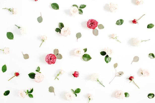 Bloemenpatroon gemaakt van rode en beige rozen, groene bladeren, takken op witte achtergrond. platliggend, bovenaanzicht