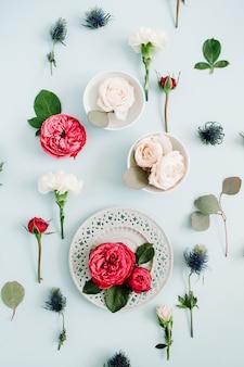 Bloemenpatroon gemaakt van rode en beige rozen op plaat, witte anjer en eucalyptustakken op bleek pastelblauw