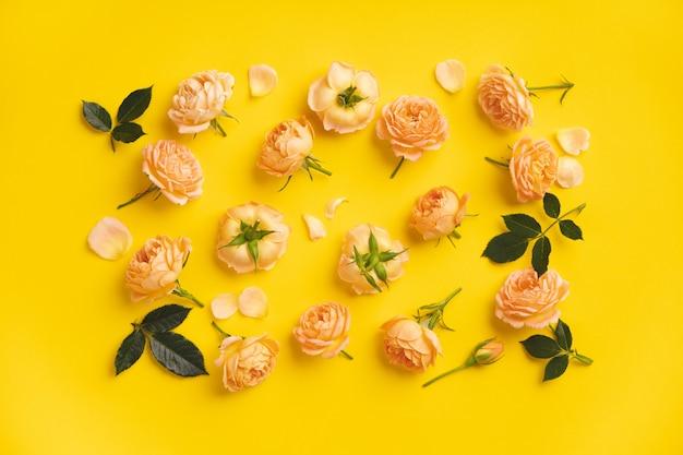 Bloemenpatroon met roze rozen en bladeren op geel