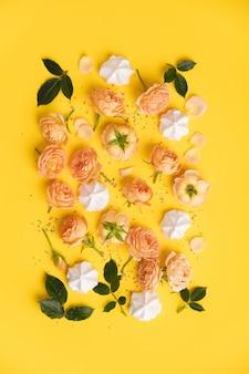 Bloemenpatroon met roze rozen en merengues op geel