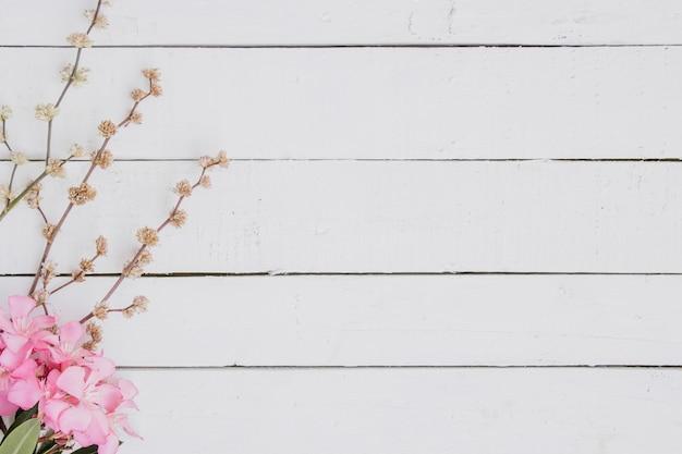 Bloemenpatroon van lichtrose takken op houten achtergrond.