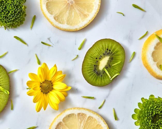 Bloemenpatroon van natuurlijke geelgroene bloemen, plakjes fruit, groene bloemblaadjes. srring natuurlijke bloeiende achtergrond.
