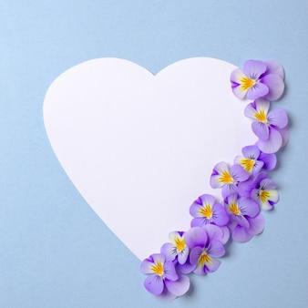 Bloemenrand van wit hartvormig papier, bloemenbloemblaadjes, groene bladeren