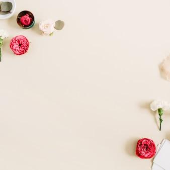 Bloemenrandkader gemaakt van beige en rode rozen en witte anjer op bleke pastelbeige