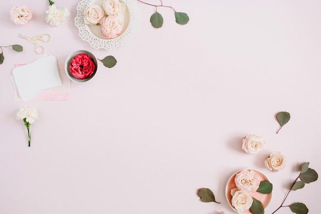 Bloemenrandkader gemaakt van beige en rode rozen en witte anjer op bleke pastelroze