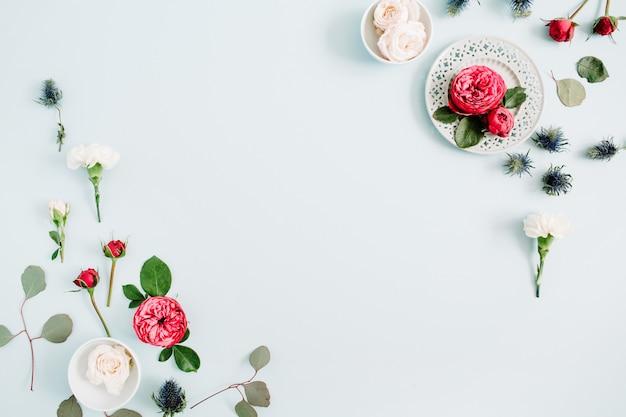 Bloemenrandkader gemaakt van rode en beige rozen, witte anjer en eucalyptustakken op bleek pastelblauw