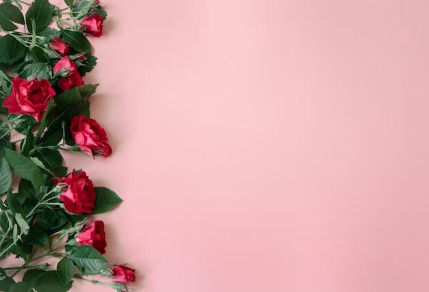 Bloemenregeling met verse rode rozen op roze achtergrondexemplaarruimte.