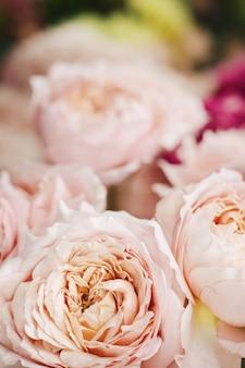 Bloemenrozenboeket op showcase in winkel. vitrinevenster met boeket en roze bloemensamenstelling in verticaal schot van de bloemistwinkel van dichtbij