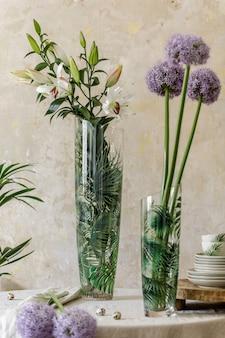Bloemensamenstelling bij keukeninterieur met houten familietafel, mooie bloemen in vaas, borden, kopjes, dienblad en elegante decoratie. eetkamer in modern huisdecor. sjabloon.