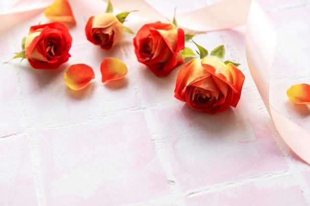 Bloemensamenstelling frame gemaakt van rode rozen en bloemblaadjes op roze tegelachtergrond