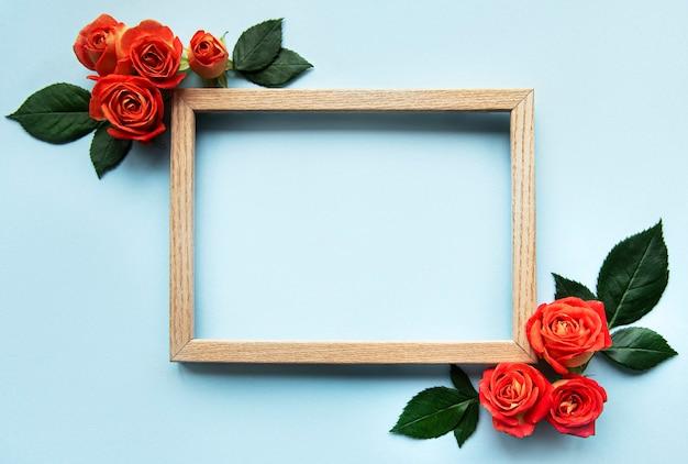 Bloemensamenstelling houten frame en rode rozen en bladeren op blauwe achtergrond