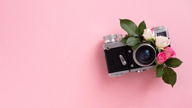 Bloemensamenstelling met een kroon van roze rozen en camera op roze achtergrond. valentijnsdag