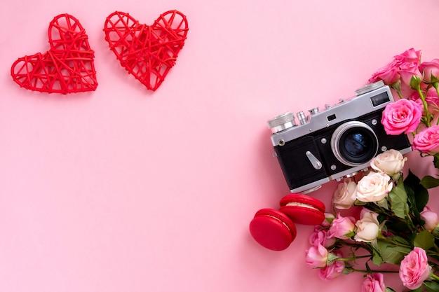 Bloemensamenstelling met een kroon van roze rozen en retro camera op roze achtergrond. valentijnsdag achtergrond. plat lag, bovenaanzicht.