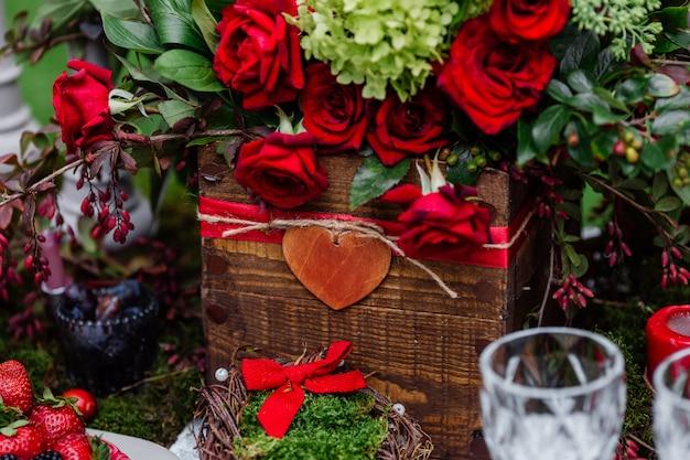 Bloemensamenstelling met rozen, bessen, kruiden en groen die zich in houten doos bevinden