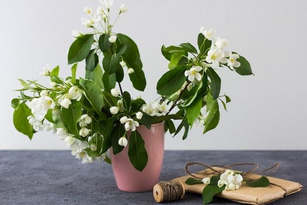 Bloemensamenstelling op een de lente zonnige dag. bloeiende takken van appelboom in een roze mini vaas op een grijze achtergrond.