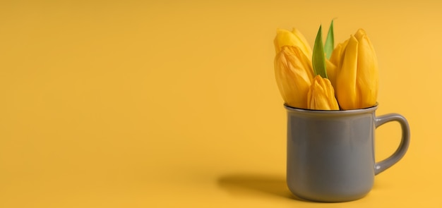 Bloemensamenstelling van gele tulpen in een theemok op een gele achtergrond, plaats van de tekst