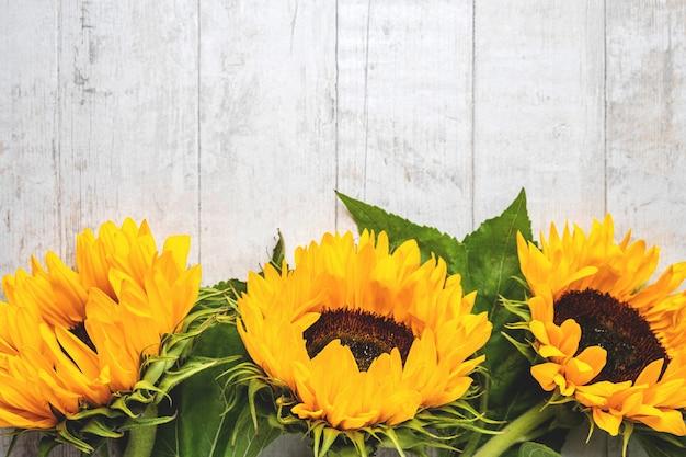 Bloemensamenstelling van gele zonnebloemen op een witte houten achtergrond.