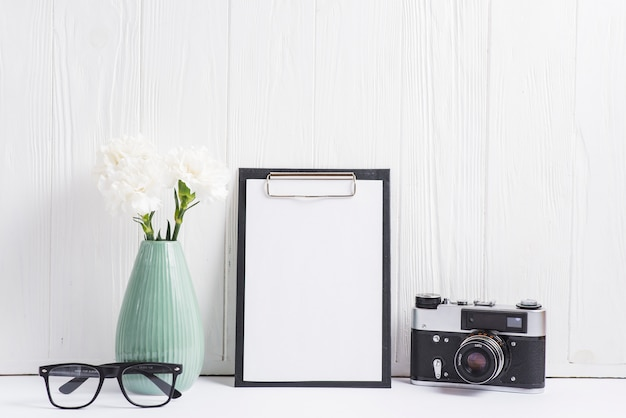 Bloemenvaas; bril; camera en blanco papier op klembord tegen lege houten muur