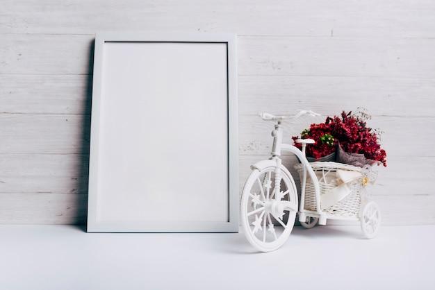 Bloemenvaas met fiets dichtbij het witte lege kader op bureau