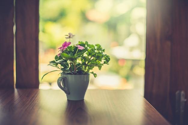 Bloemenvaas op de tafel bij het raam