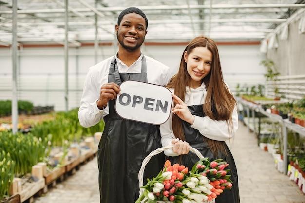 Bloemenverkopers met een bordje. tuinmannen in schorten. veel tulpen in een kas.