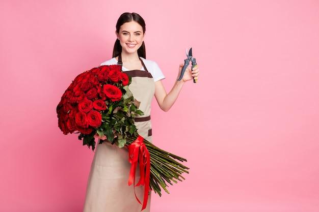 Bloemenwinkel assistent dame houd rozen bos afgeknipte uiteinden met schaar