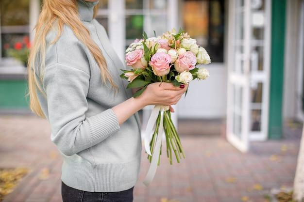 Bloemenwinkel bij daglicht. een vrouw houdt een mooi boeket bloemen vast