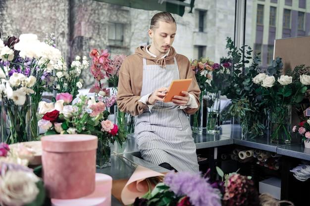 Bloemenwinkel. oplettende uitgaven van ontwerpers pauzeren met gadget terwijl ze naar nieuws kijken