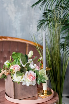 Bloemenwinkel. vintage compositie met ingemaakte bloemen, vazen, kaarsen en planten. concept van bruiloft decor. mooie bloemen, houten kist en lange kaars in klassieke vintage opengewerkte kandelaar