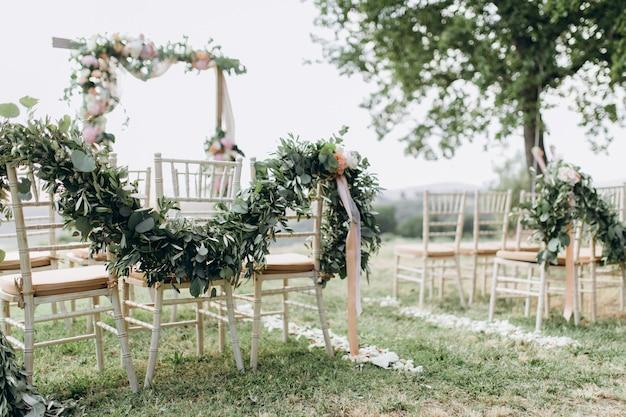 Bloemige composities gemaakt van groen bij de buiten huwelijksceremonie