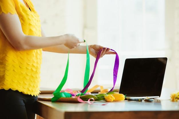 Bloemist aan het werk: vrouw laat zien hoe je een boeket met tulpen maakt.