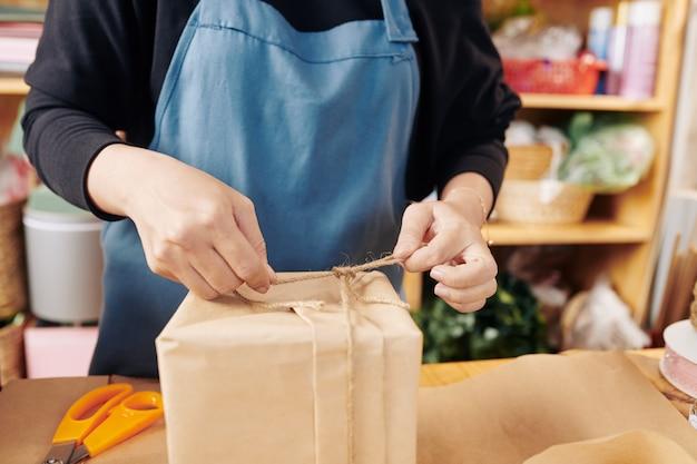 Bloemist bindende boog na het verpakken van geschenkdoos