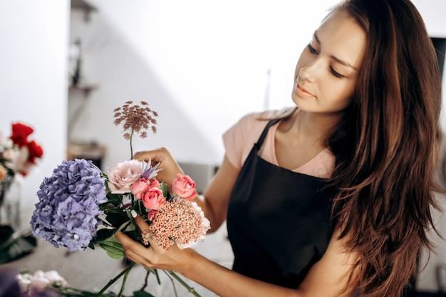 Bloemist collecties een boeket verse roze kleine rozen, blauwe hortensia en andere bloemen in de bloemenwinkel.